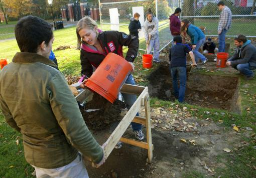 Five gallons of possibility - Sophomore Monica Roth delivers a budket of excavated dirt to the sifter, part of a systematic search for pottery sherds, bits of brick, or any other evidence of an 18th-century structure.