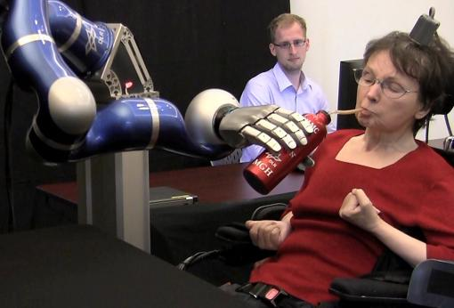 One small step - A 58-year-old woman, paralyzed by a stroke for almost 15 years, uses her thoughts to control a robotic arm, grasp a bottle of coffee, serve herself a drink, and return the bottle to the table.
