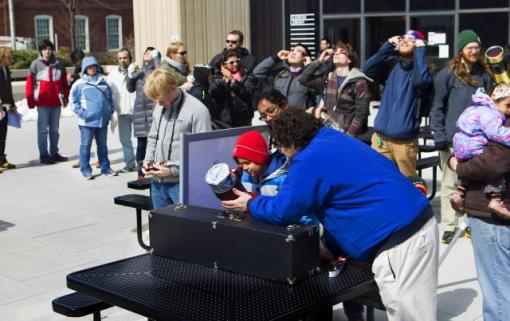 A safe sight of spring - Ian Dell'antonio assists Raja MacNeal, 7, of Providence, in using a white-light solar telescope to view Tuesday's vernal equinox on the patio of the Science Library.