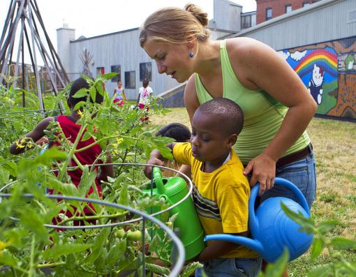 How — and why — does the garden grow? - Rising senior Mary Alice Reilly helps a young gardener give the plants a drink. The learning is constant and effective at the John Hope Settlement House — for preschoolers and Brown students alike.