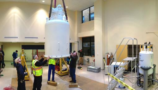 The only way in - Workers guide a 3.8-ton, $2.9-million magnet as it is lowered through the roof into place at the Structural Biology Core Facility. The new magnet is almost twice as powerful as the University's earlier instrument, to the right. (View the crane's eye video below.)