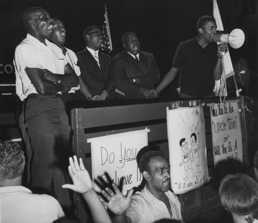 "Emancipation Day, 1966. - Cliff Monteiro, Rev. Virgil Woods, and others lead a crowd of at least 500 in ""We Shall Overcome"" at a Southside freedom rally at the Willard Avenue Shopping Center.  The rally followed local marches against the deterioration of local housing."