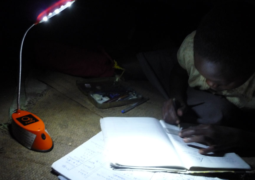 'You will learn from and others will learn from you.': Chishio Furukawa, a 2011 BISP fellow, studied how replacing kerosene lamps with solar-powered lights might benefit people like this student in Uganda. Credit: Chishio Furukawa/Brown University