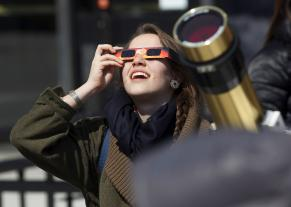 Lower-tech: Mali'o Kodis '14 views the sun through an inexpensive pair of paper solar viewing glasses.