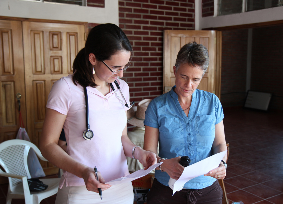 """We exist to serve the poor"": Brown doctors and students visit a few times a year, but Honduran health care providers run day-to-day operations. The Gauchipilincito clinic now has a full-time nurse, community health promoter and educator, and a security guard. Emily Harrison confers with Jodi Roque, a family medicine house staff officer at Memorial Hospital."