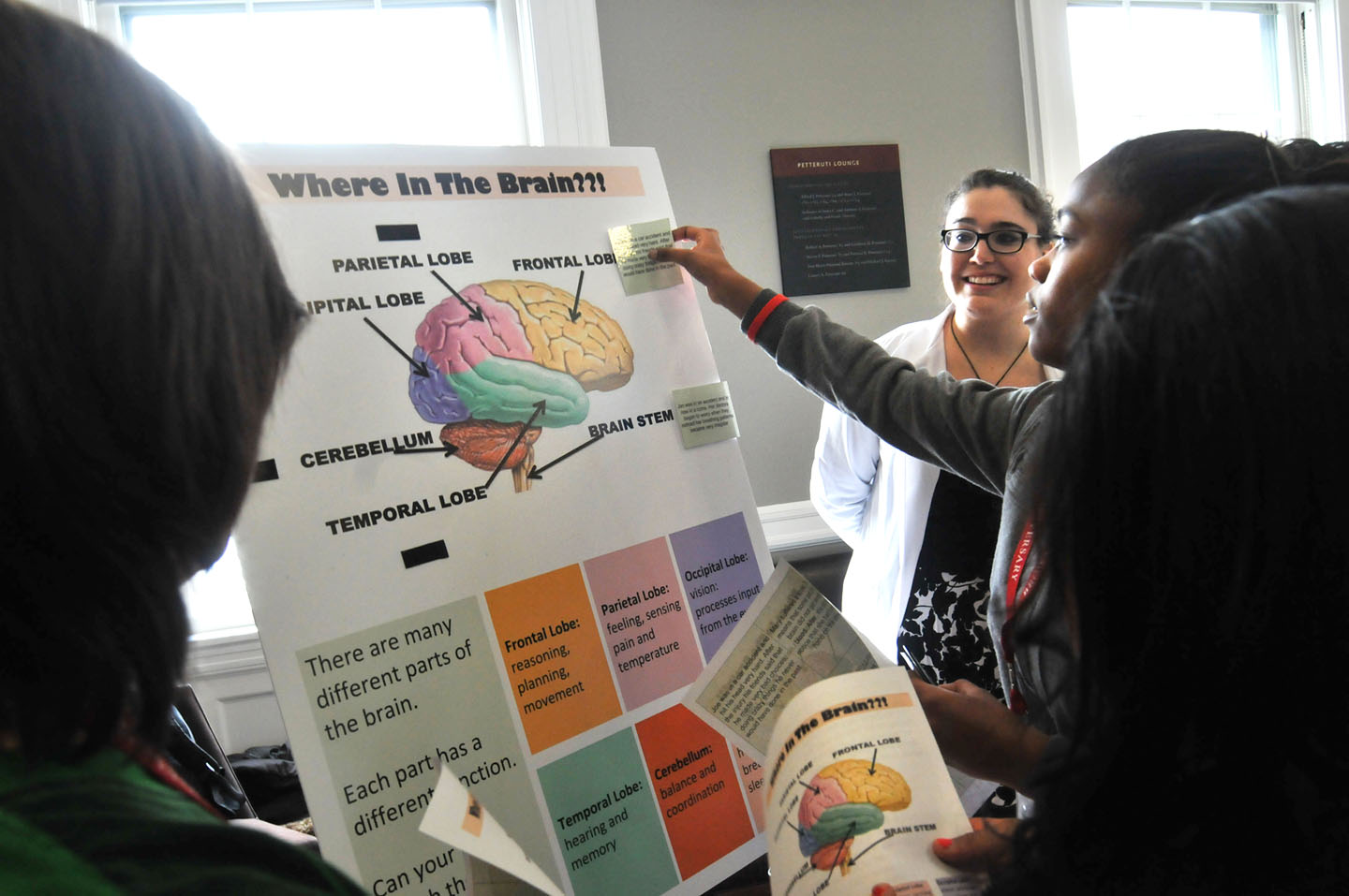 Pin the sticker on the brain: Medical student Zoe Weiss leads a session on the geography of the brain, asking middle school students to match a problem with the region of the brain that's involved. Credit: Frank Mullin/Brown University